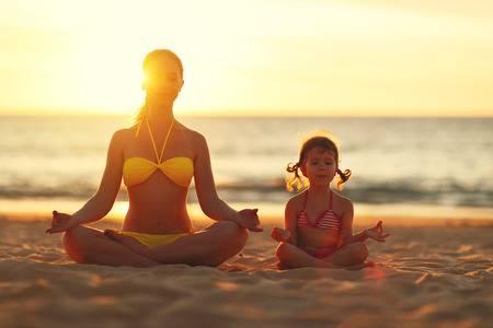 75486172-madre-e-hija-familia-feliz-niño-hacer-yoga-meditar-en-posición-de-loto-en-la-playa-al-atardecer