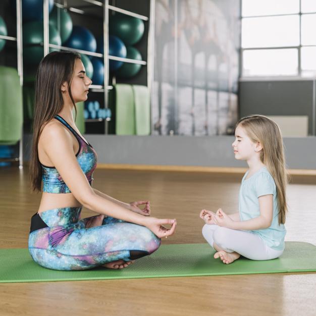 madre-e-hija-meditando-juntas-sobre-estera-yoga-sobre-piso-madera_23-2148185913